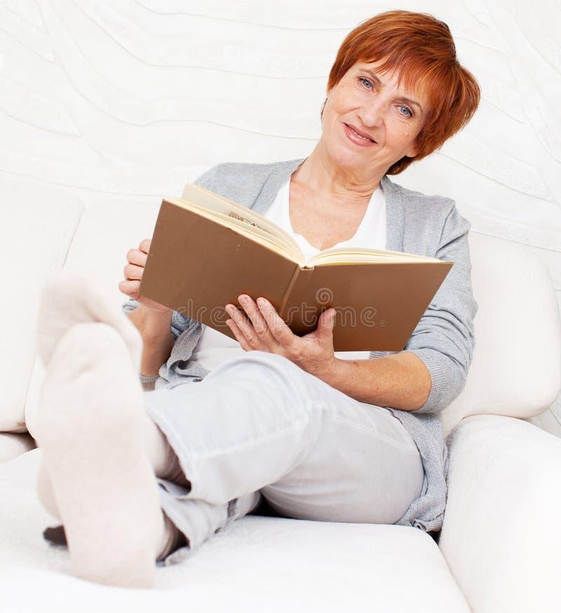 Het volwassen rijpe boek van de vrouwenlezing stock foto