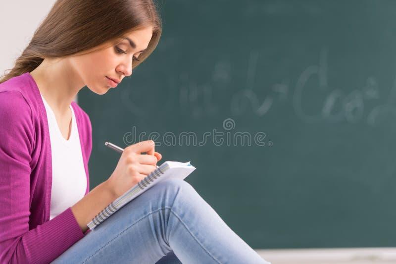 Het volwassen studentenmeisje zitting en schrijven stock afbeeldingen