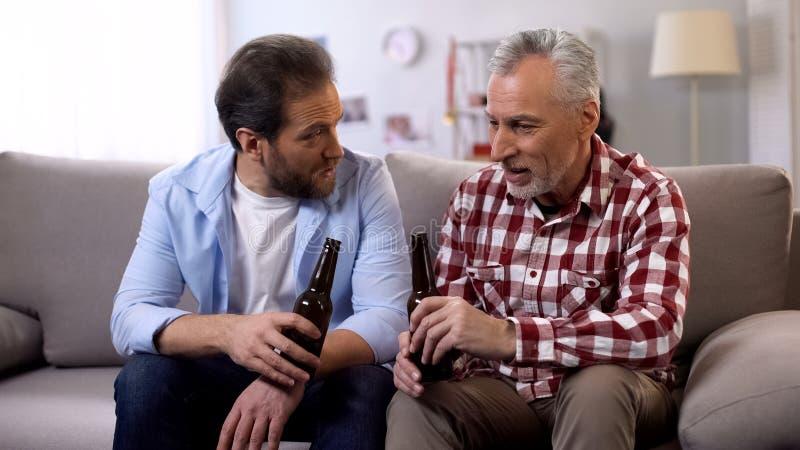 Het volwassen vader en zoons ontspannen op weekend het drinken bier en het spreken, samenhorigheid stock foto