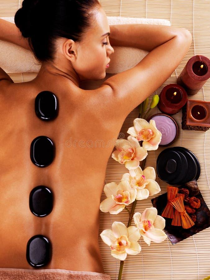 Het volwassen vrouw ontspannen in kuuroordsalon met hete stenen op lichaam stock foto