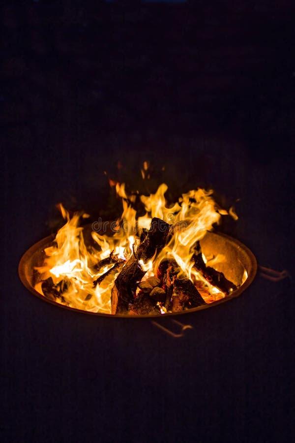 Het vonken van kampbrand in dark stock fotografie