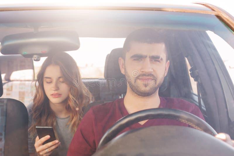 Het vooraanzicht van geconcentreerde mannelijke bestuurder zit bij wiel en drijft auto terwijl zijn meisje op achterbank zit, sli royalty-vrije stock foto
