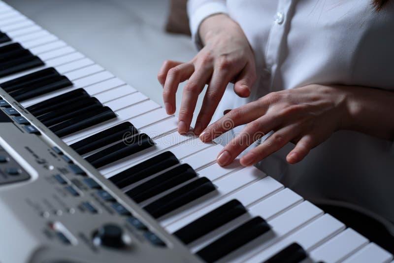 Het vooraanzicht van vrouwelijke handen praktizeerde speel de synthesizer stock foto's