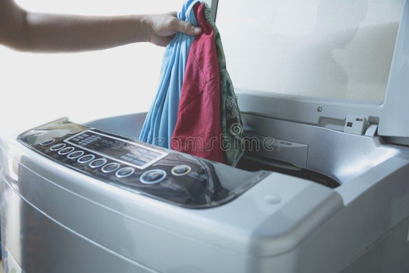 Het voorbereiden van de wascyclus Wasmachine, Hand met kleren stock afbeelding