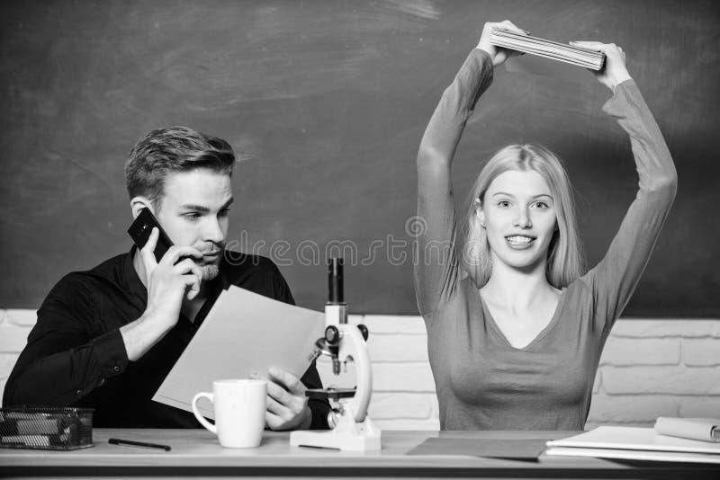 Het voorbereiden van een les Mooie leraar en knappe schoolmeester die documenten sorteren Universiteit of studenten Paar stock fotografie