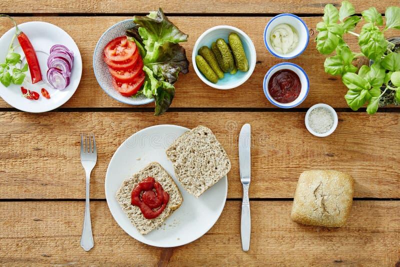 Het voorbereiden van een veganistsandwich die tomatoe saus op bredrole zetten royalty-vrije stock afbeelding