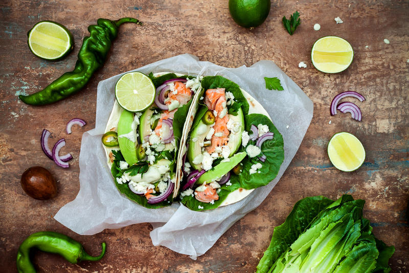 Het voorbereiden van gezonde lunchsnacks Vissentaco's met geroosterde zalm, rode ui, de verse saladebladeren en saus van de avoca royalty-vrije stock foto