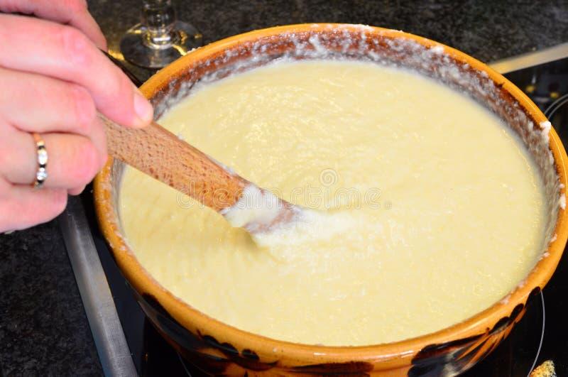 Het voorbereiden van kaasfondue stock afbeelding