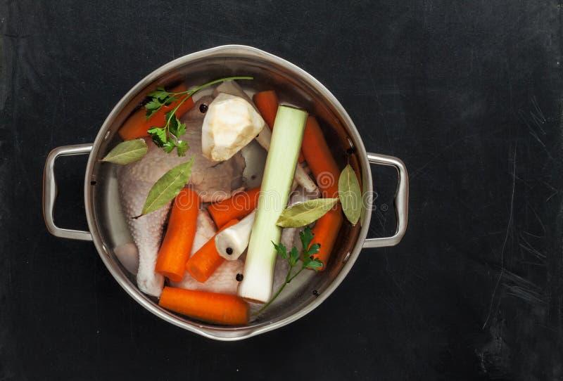 Het voorbereiden van kippenvoorraad met groenten (bouillon) in een pot stock afbeelding