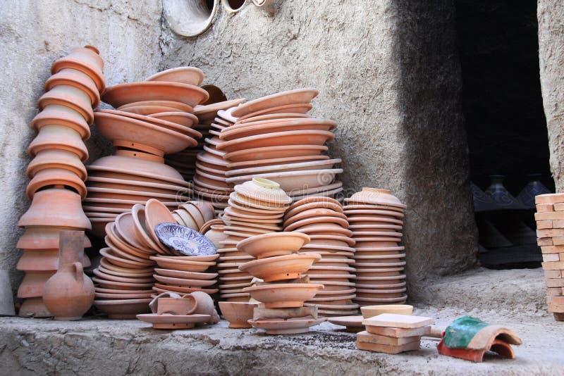 Het voorbereiden van kleiaardewerk voor vuren in adobeoven, Fez, Marokko stock foto's