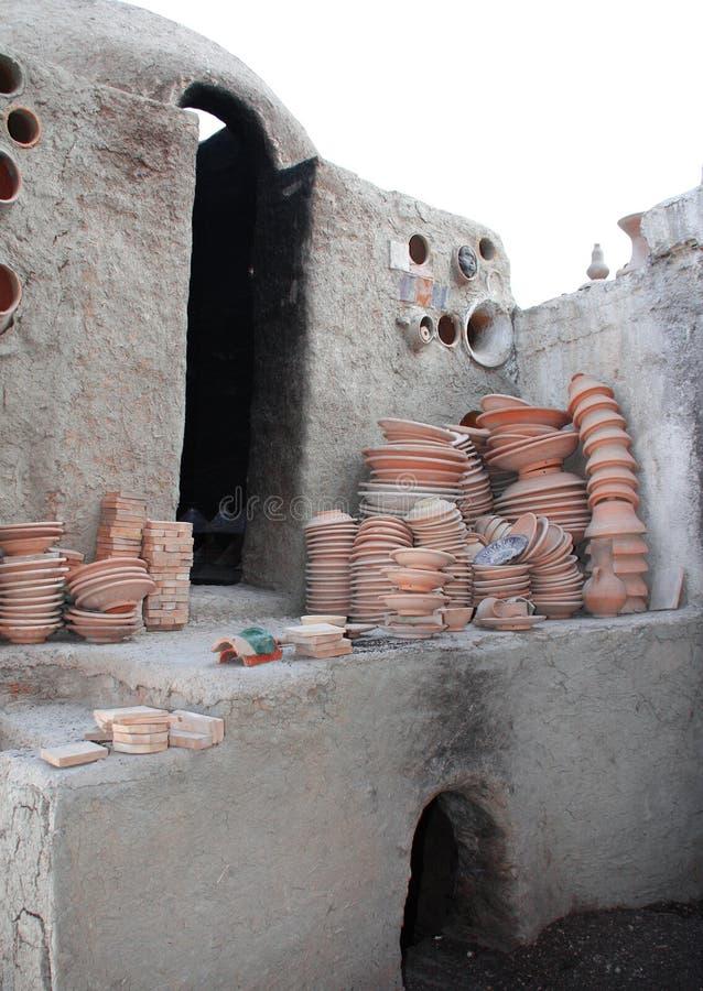 Het voorbereiden van kleiaardewerk voor vuren in adobeoven, Fez, Marokko stock fotografie