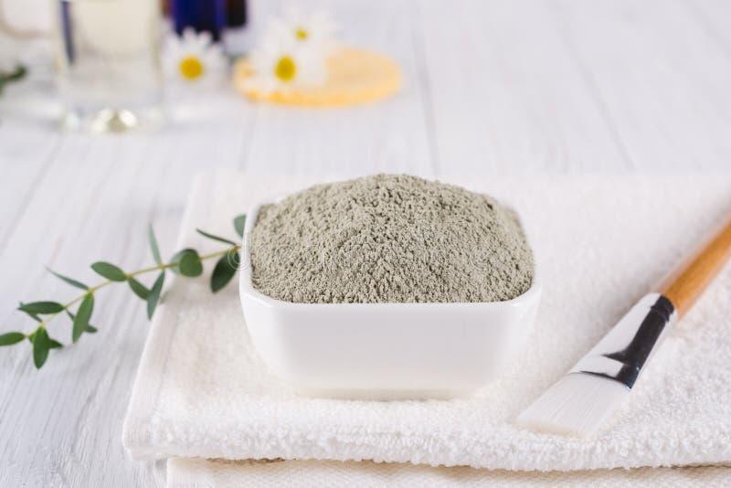 Het voorbereiden van kosmetisch moddermasker met diverse skincareproducten Droog kleipoeder in kom De natuurlijke schoonheidsmidd royalty-vrije stock afbeelding