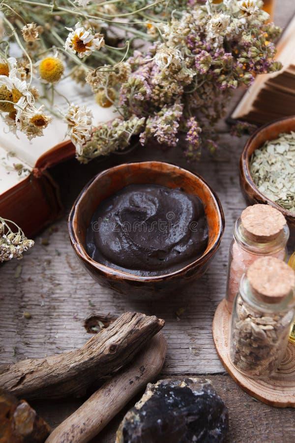 Het voorbereiden van kosmetisch zwart moddermasker in ceramische kom op uitstekende houten achtergrond Vooraanzicht van gezichtsk royalty-vrije stock foto's