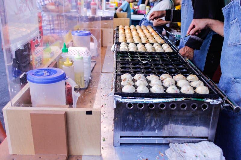 Het voorbereiden van stoombroodjes bij nachtmarkt stock foto
