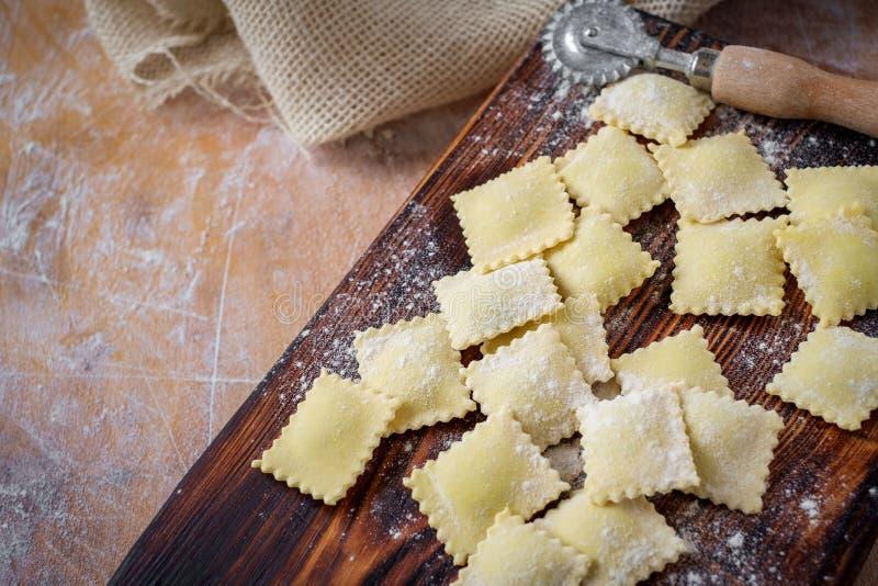 Het voorbereiden van verse eigengemaakte ravioli bij de keuken houten lijst met bloem stock foto