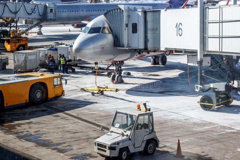 Het voorbereidende werk dichtbij het vliegtuig bij de luchthaven stock afbeeldingen