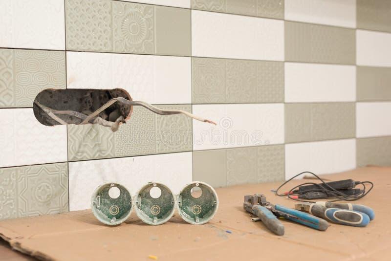 Het voorbereidingen treffen om een elektroafzet te installeren Close-up van professionele elektricienhulpmiddelen en elektroafzet royalty-vrije stock afbeelding