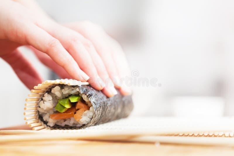 Het voorbereidingen treffen, rollende sushi Zalm, avocado, rijst en eetstokjes op houten lijst royalty-vrije stock afbeelding