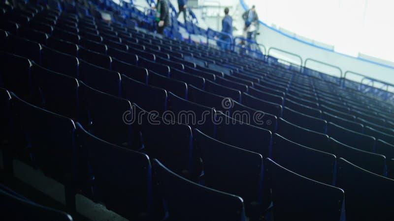 Het voorbereidingen treffen voor een hockeygelijke Organisatoren die rondwandelen Lege tribunes stock afbeelding