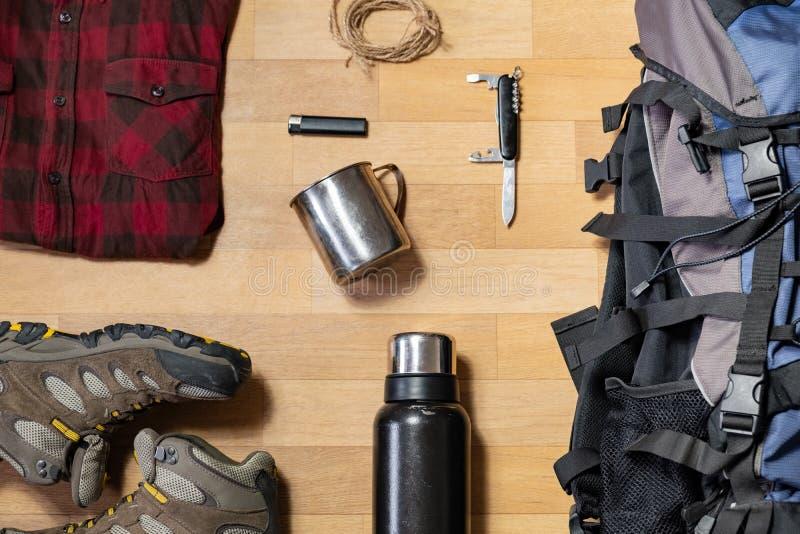 Het voorbereidingen treffen voor een wandelingsreis: de backpacking dingen en klerenvlakte lag stock foto