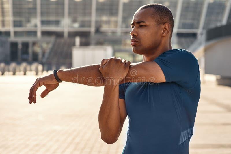 Het voorbereidingen treffen voor training Sluit portret die van Afrikaanse atleet zijn wapens omhoog uitrekken tijdens ochtendtra stock foto