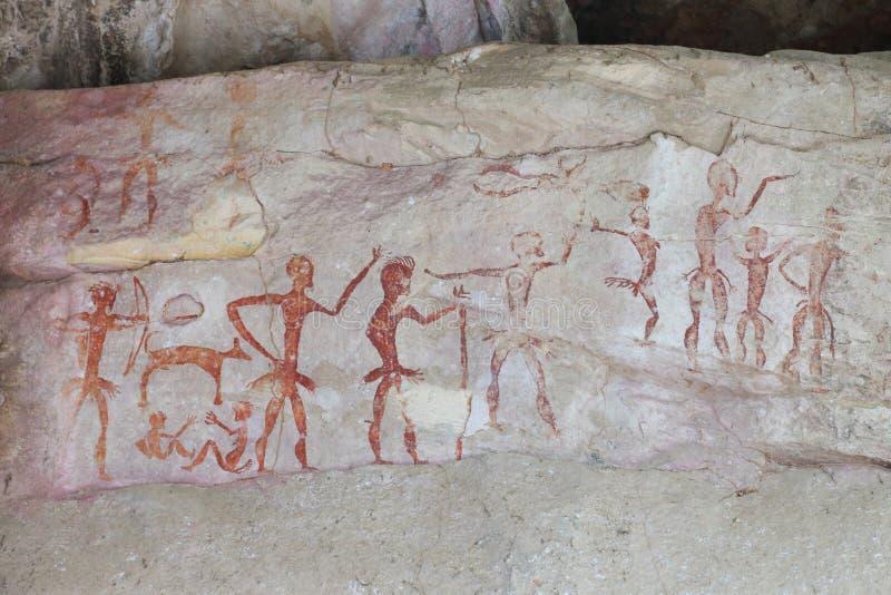 Het voorhistorische schilderen door primitieve lokale holbewoner op de steenmuur die de jacht en de beschaving tonen meer dan 400 royalty-vrije stock afbeeldingen