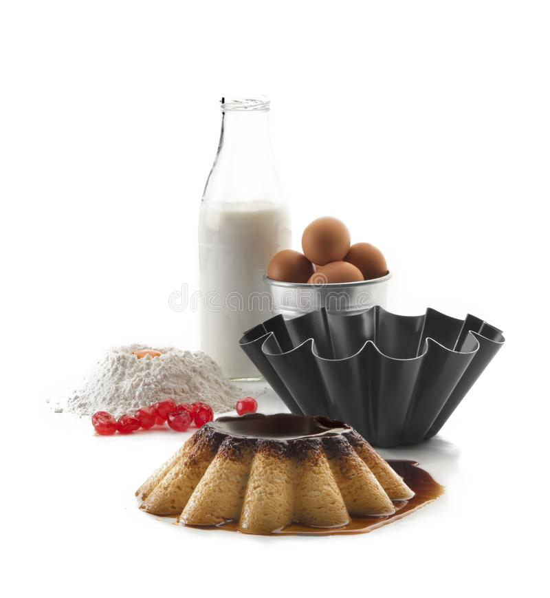 Het voorstilleven die uit een fles melk, bloem, eierdooier, eieren in een kom bestaan, krulde vorm en een vlaai in de voorgrond stock foto