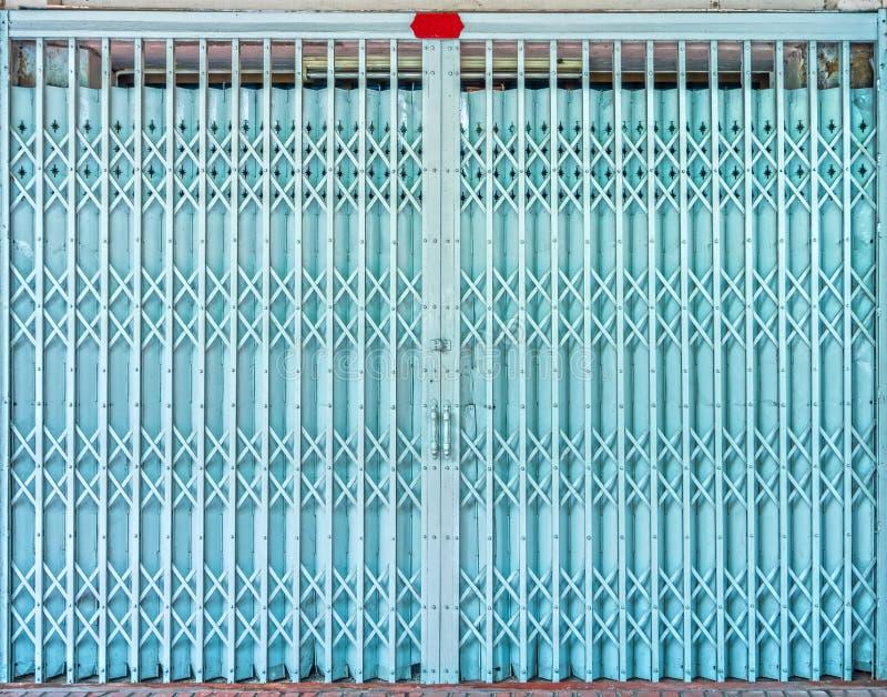Het vouwen van de oude blauwe poort van de metaaldeur stock fotografie