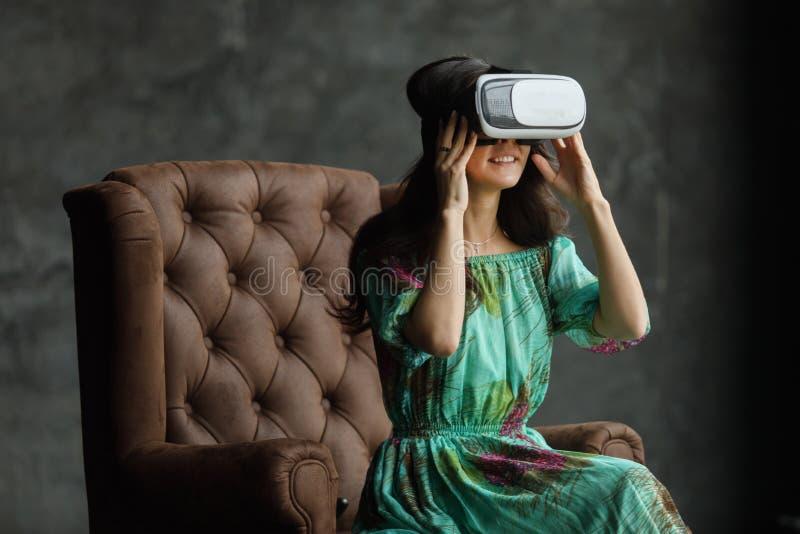 Het VR-hoofdtelefoonontwerp is generisch en geen emblemen, Vrouw met glazen van virtuele werkelijkheid, zit als voorzitter, tegen royalty-vrije stock afbeelding