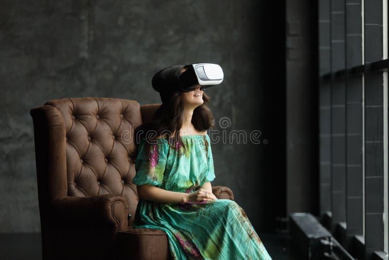 Het VR-hoofdtelefoonontwerp is generisch en geen emblemen, Vrouw met glazen van virtuele werkelijkheid, zit als voorzitter, tegen stock foto's