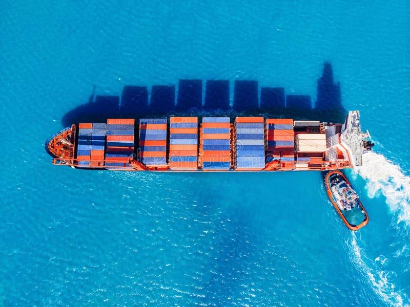 Het vrachtschip gaat handelhaven in, legt de sleepboothulp aan pijler vast Logistiekconcept, vervoeroverzees stock afbeeldingen