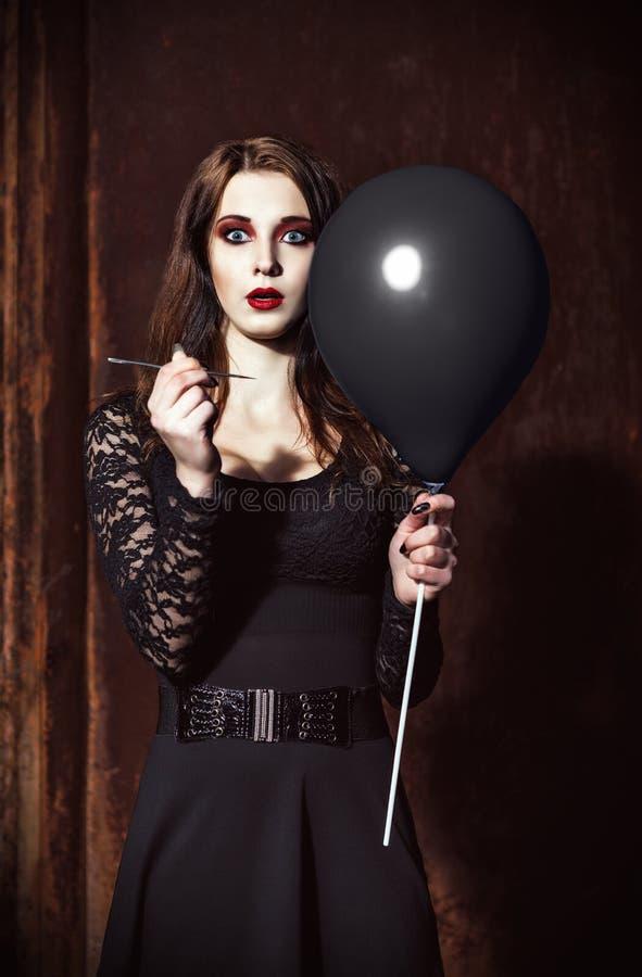 Het vreemde doen schrikken meisje doordringt ballon door naald stock foto