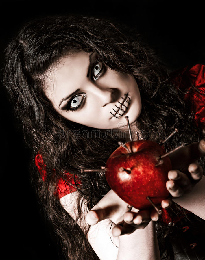 Het vreemde enge meisje met genaaide mond gesloten die houdt appel met spijkers wordt beslagen royalty-vrije stock fotografie
