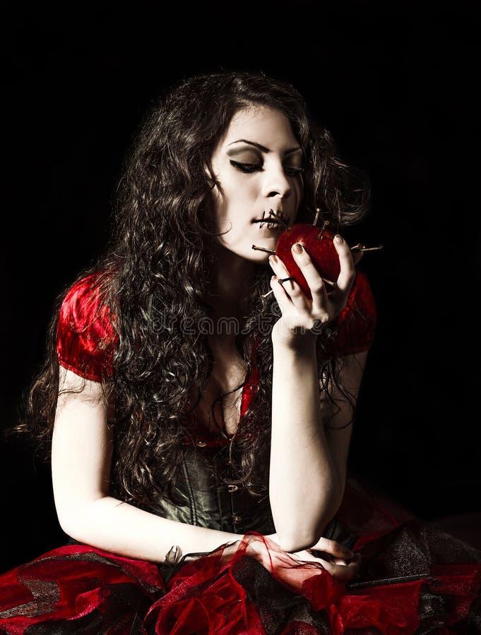Het vreemde enge meisje met genaaide mond gesloten probeert die een appel te eten met spijkers wordt beslagen stock fotografie