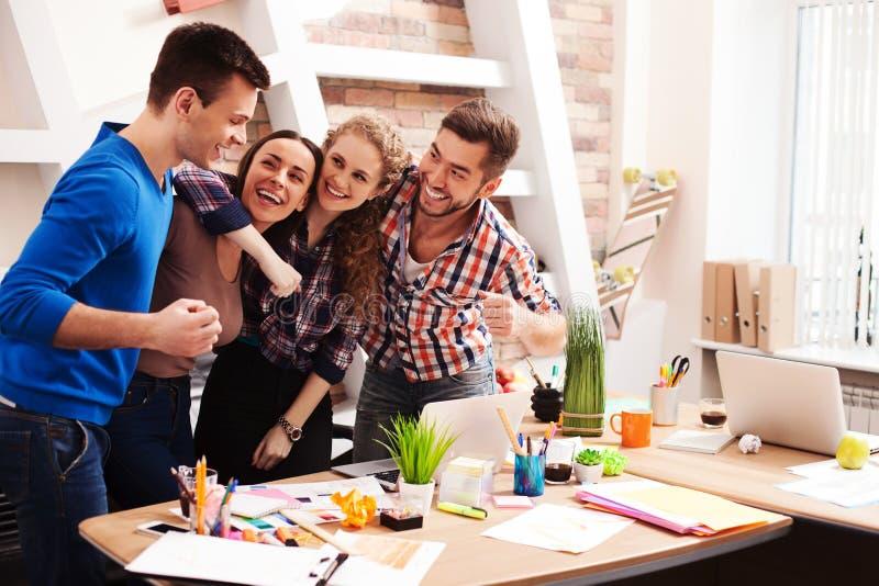 Het vriendschappelijke creatieve team drukt positieve emoties uit stock fotografie