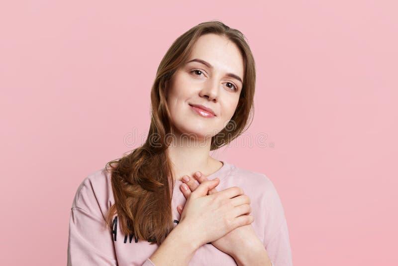 Het vriendschappelijke donkerbruine wijfje houdt handen op hart, uitdrukt goed gevoel, heeft prettige die verschijning, over roze stock afbeeldingen
