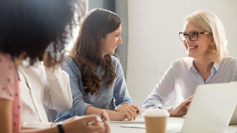Het vriendschappelijke het glimlachen oude en jonge onderneemsters spreken die bij vergadering lachen royalty-vrije stock afbeelding