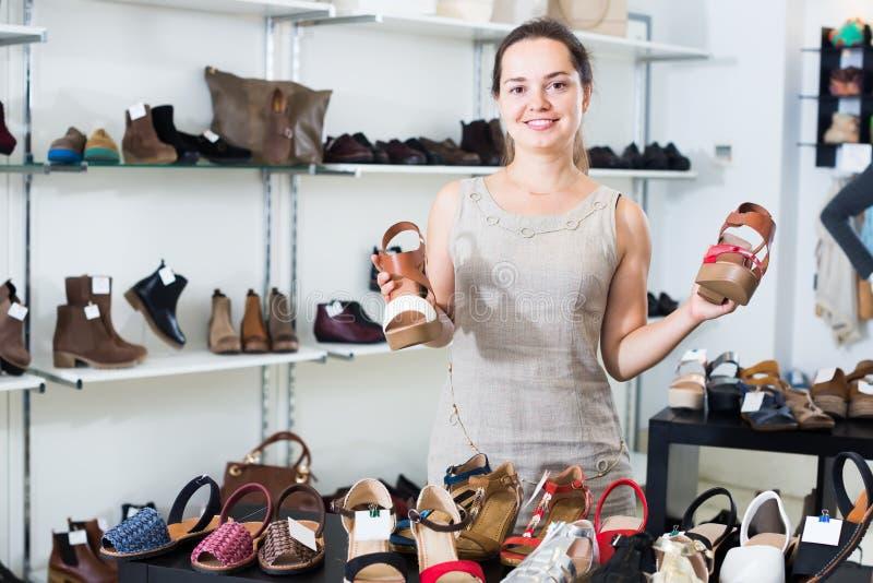 Het vriendschappelijke het meisje van de schoeiselwinkel stellen met verschillende schoenen stock afbeelding