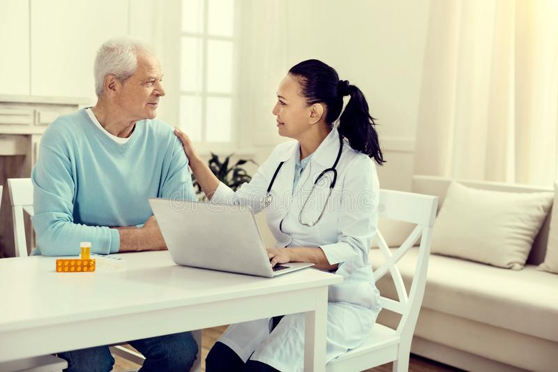 Het vriendschappelijke kijken arts die aan bejaarde tijdens overleg spreken stock afbeelding