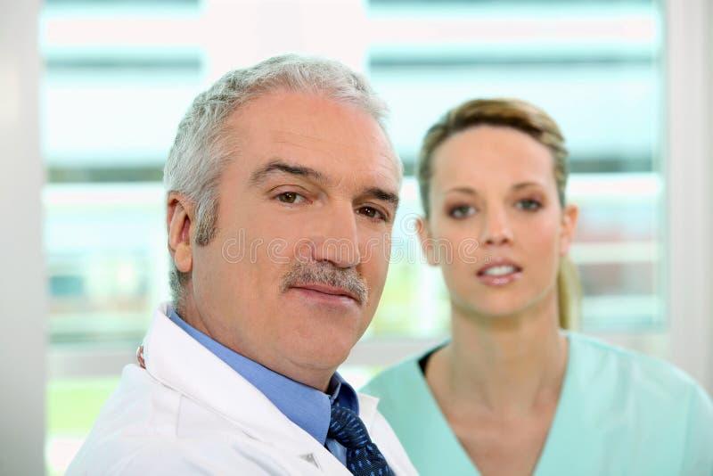 Het vriendschappelijke kijken arts en verpleegster royalty-vrije stock afbeelding