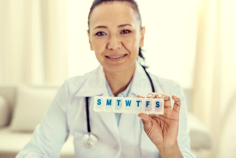 Het vriendschappelijke kijken verpleegster die medicijndoos tonen in camera royalty-vrije stock afbeeldingen