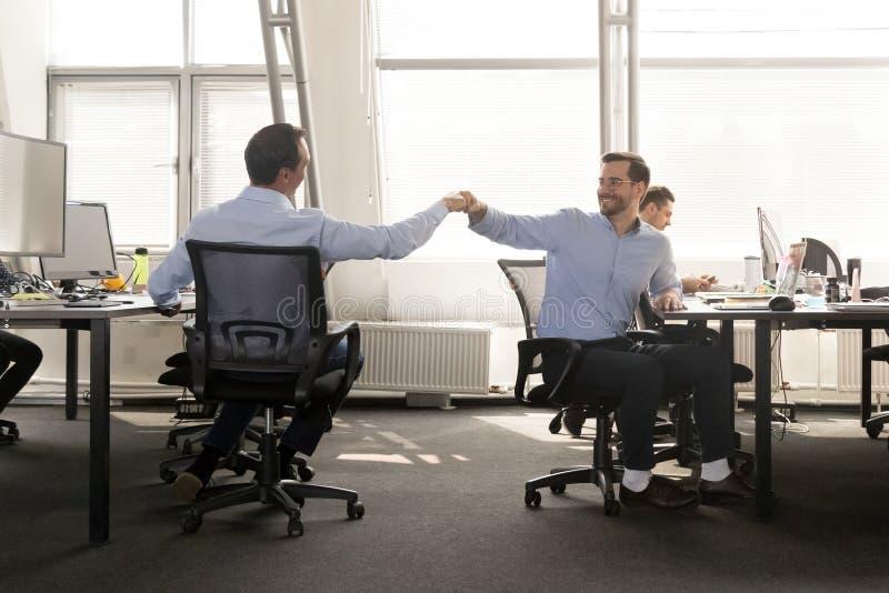 Het vriendschappelijke mannelijke vriendenvuist stoten op het werk viert goede teamwo royalty-vrije stock fotografie