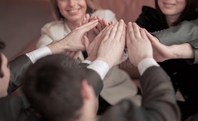Het vriendschappelijke professionele commerciële team, tevreden met zijn overwinning, handen clasped samen stock afbeeldingen