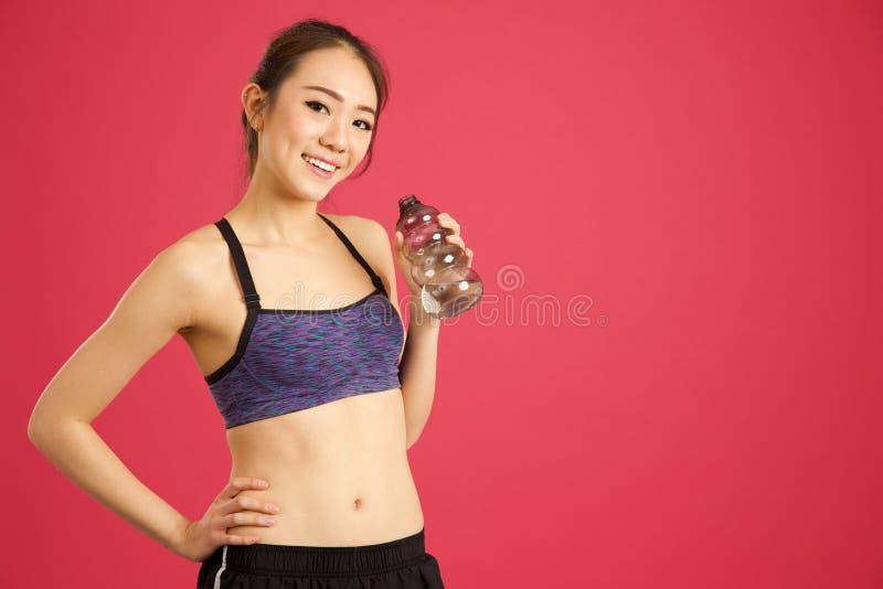 Het vrij Aziatische meisje in de fles van het studio drinkwater na werkt uit royalty-vrije stock afbeeldingen