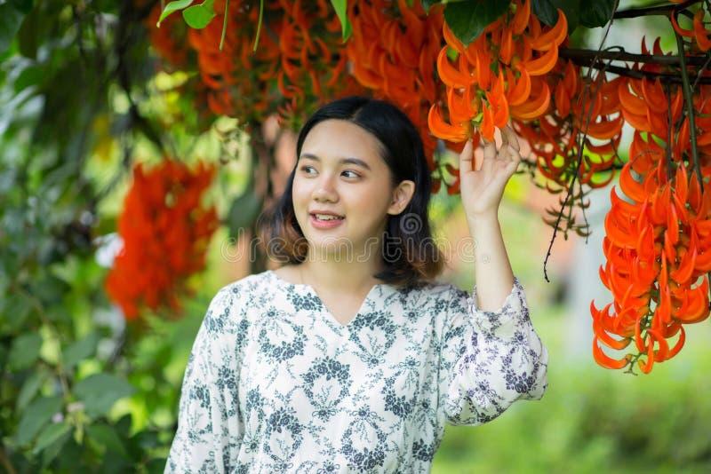 Het vrij Aziatische meisje geniet van met bloemen stock afbeeldingen