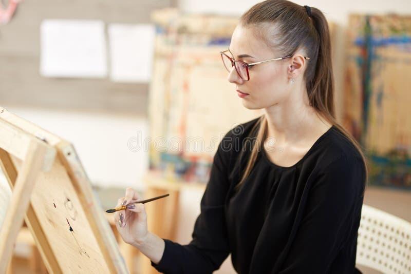 Het vrij blonde meisje in glazen gekleed in zwarte blouse zit bij de schildersezel en schildert een beeld in de kunststudio royalty-vrije stock foto's