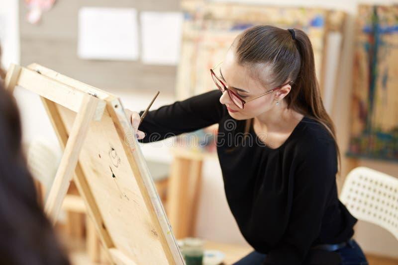 Het vrij blonde meisje in glazen gekleed in zwarte blouse zit bij de schildersezel en schildert een beeld in de kunststudio stock afbeelding