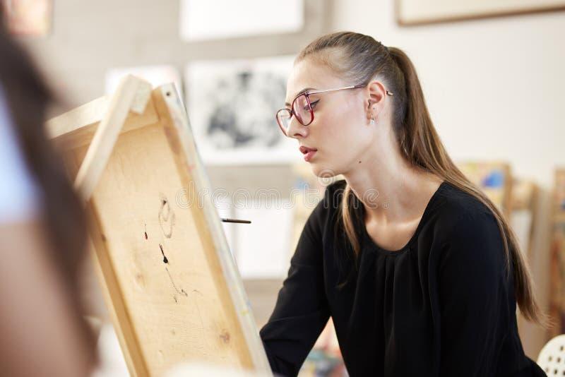 Het vrij blonde meisje in glazen gekleed in zwarte blouse zit bij de schildersezel en schildert een beeld in de kunststudio stock fotografie