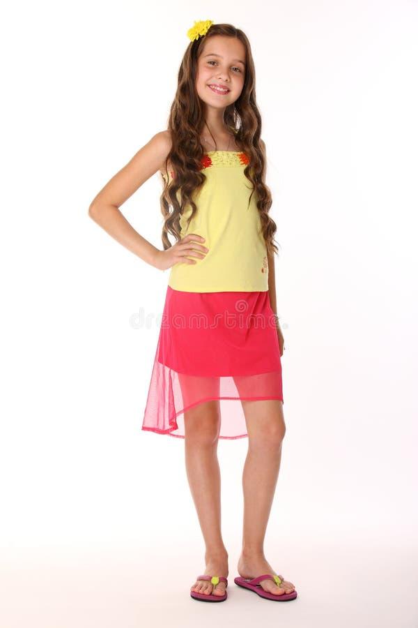 Het vrij donkerbruine kindmeisje is tribunes in een rode rok met naakte benen en glimlacht stock foto