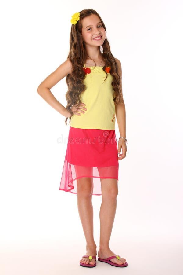 Het vrij donkerbruine kindmeisje is tribunes in een rode rok met naakte benen en glimlacht royalty-vrije stock foto's